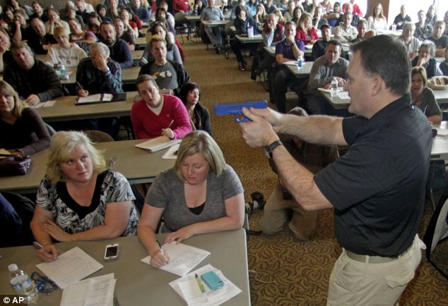 Around 200 teachers watched intently and made notes as Mr Aposhian demonstrated with a plastic gun during concealed-weapons training offered free in the wake of the Sandy Hook massacre