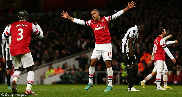Jump for joy: Theo Walcott celebrates after helping Arsenal regain the lead for a fourth time
