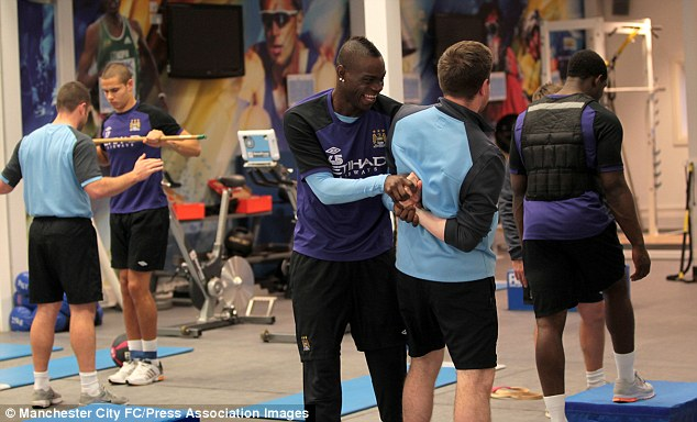 Larking about: Mario Balotelli (centre) has a joke in the gym during training