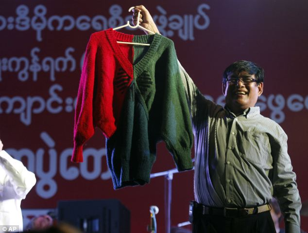 Presenters show a hand-knit woolen sweater, made by Myanmar opposition leader Aung San Suu kyi, during an auction at a fundraising concert