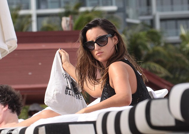 Family affair: Lily is vacationing in Miami Beach with her twin sister Rosie and their mother, but stepped out for some solo sunbathing on Saturday