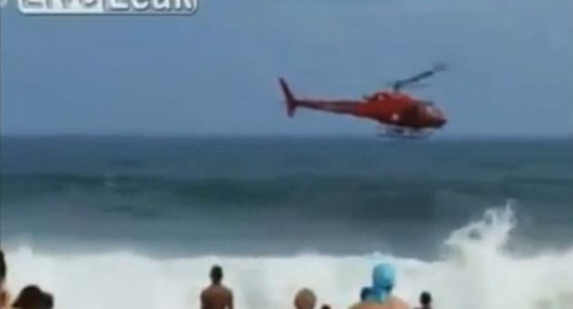 ... Going... : The red helicopter slowly begins to drop towards the sea with thousands of stunned beachgoers looking on