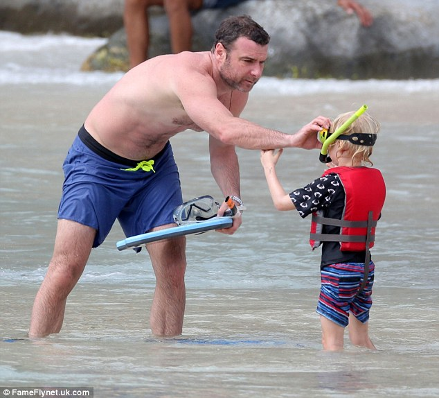 Ducking and diving: Liev helps his little man get his goggles in place ready for their aquatic adventure