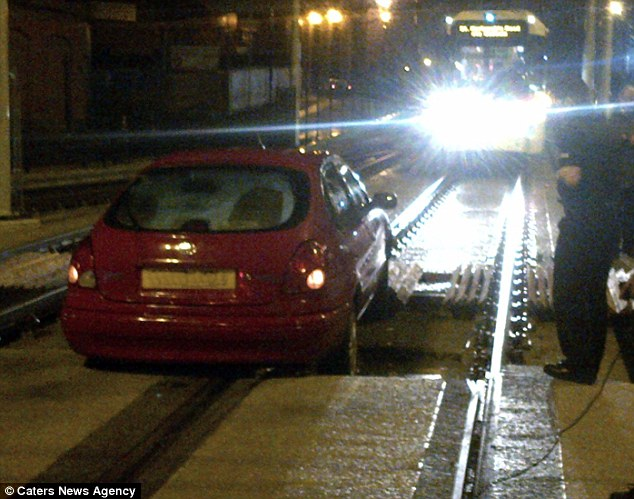 The tram managed to stop just yards away from the red Toyota after it became stuck on tracks near Oldham