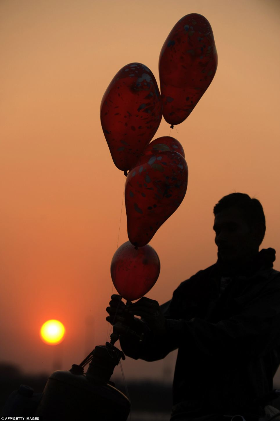 An Indian vendor inflates balloons as the sunsets in Siliguri, West Bengal, India
