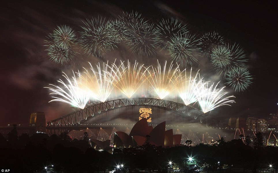 Extravagant: Sydney's balmy summer night was lit up by 7 tons of fireworks which were fired from roof tops and barges, many cascading from the Sydney Harbour Bridge
