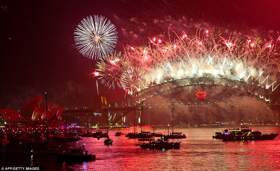 Colourful: Spectator boats in Sydney Harbour look on as the New Year's Eve fireworks erupt over the Sydney Harbour Bridge