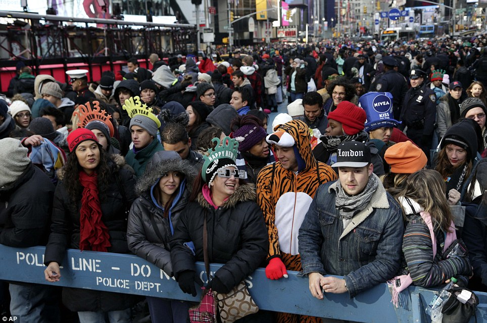 Eager: Thousands have already arrived in Times Square, New York.  An estimated 1 million people are expected to cram into the area to see the crystal ball drop