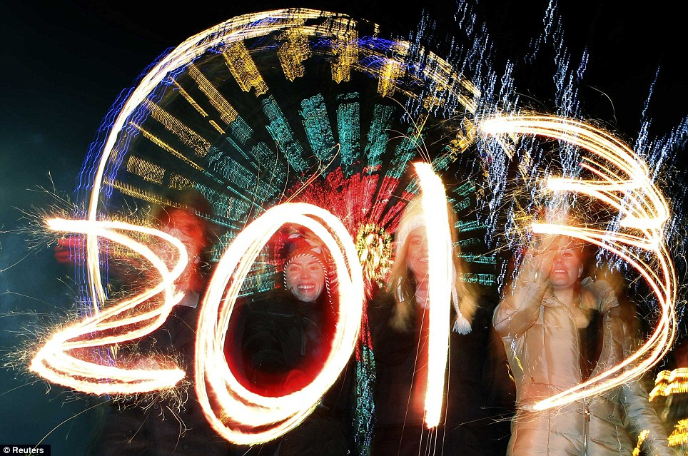 Happy: Revellers write the number 2013 with sparklers during the Hogmanay street party celebrations in Edinburgh