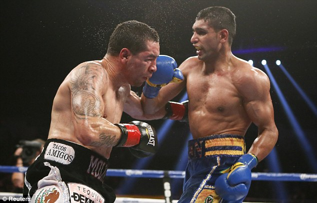 Back on track: Amir Khan (right) stopped Carlos Molina to end a disappointing year on a high