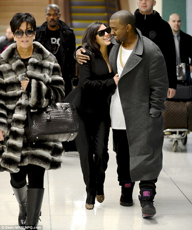 So happy: The pair cuddle up as they jet out of LAX a few hours before the party, with Kris Jenner in tow
