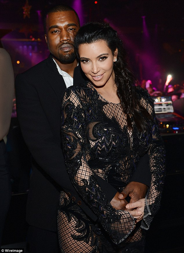 Hand on her stomach: Kanye puts his hands on his girlfriend's stomach, protective of her pregnancy bump