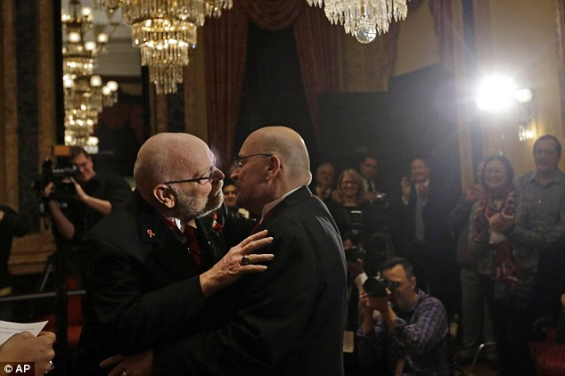 Forever love: James Scales, left, and William Tasker, who have been together for 35 years, kiss after getting married shortly after midnight on January 1