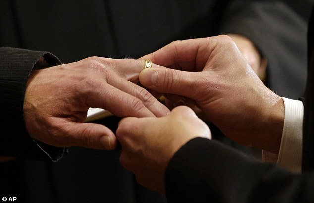 True love: Thomas Rabe, right, places a wedding ring on Robert Coffman's finger during their marriage ceremony shortly after midnight
