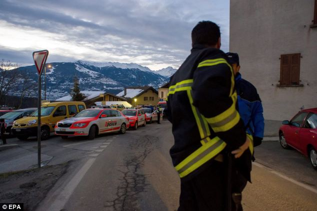 Deadly attack: Swiss police begin their investigation in Daillon today, after three people were shot dead in the village last night