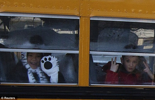 Back to school: Sandy Hook students wave on their way to their new school, with one young boy holding up his fingers in a sign Americans recognise as a peace sign