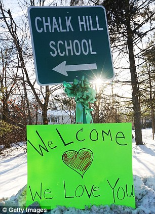 A sign reads 'Welcome We Love You' beneath a sign pointing to the location of Chalk Hill School