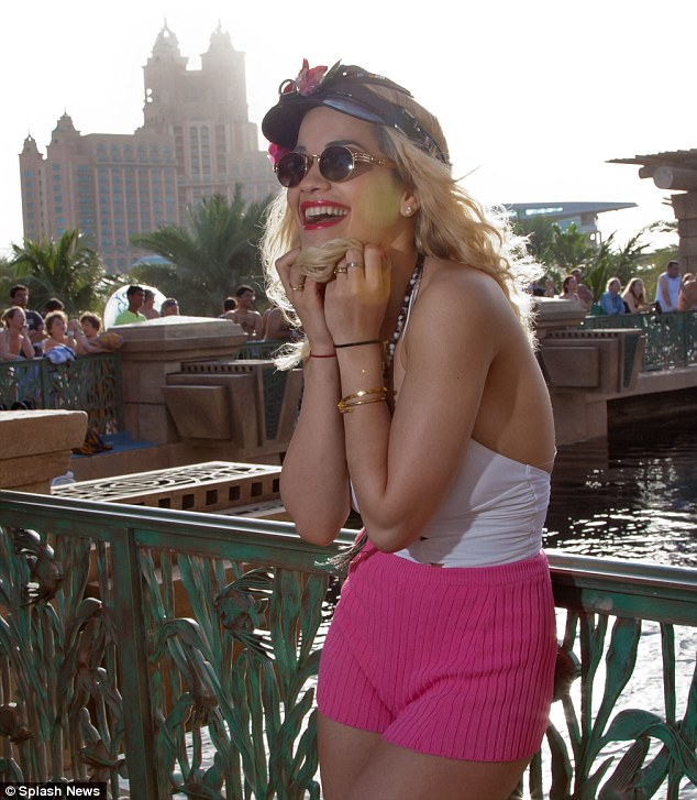 Smiles all round: Rita looked in good spirits as she posed up in a pair of pink shorts and a white swimming costume in front of the hotel