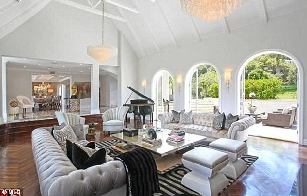 Contemporary: The mansion features wood-beamed cathedral ceilings, chandeliers and walnut floors