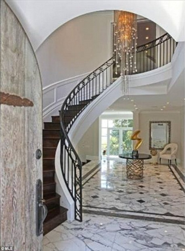 Elegant: A curving staircase with wrought iron railing leads the way upstairs