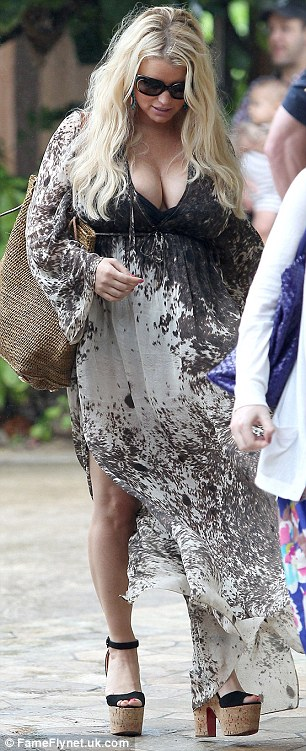 Walking tall: The reality star was out enjoying a meal with her family and friends on the Oahu island and completed her flowing dress with platform heels and shades