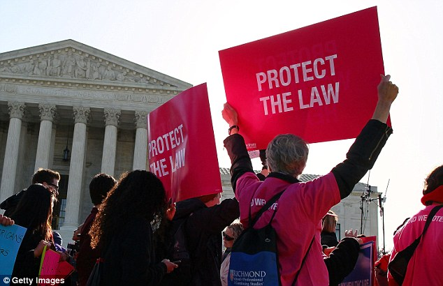 People participate in a protest on the second day of oral arguments for the Patient Protection and Affordable Care Act in front of the U.S. Supreme Court in March 2012. The law was approved by the court but insurance costs are still rising for some