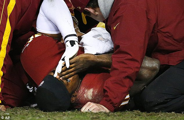 Jeopardy: Griffin is examined by team officials as he writhes in pain on the field