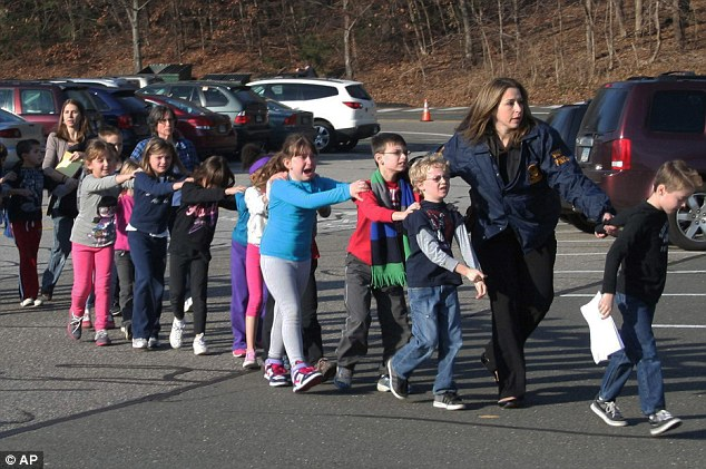 Iconic: These image of police officers and teachers leading children to safety immediately after the Sandy Hook massacre was seen around the world