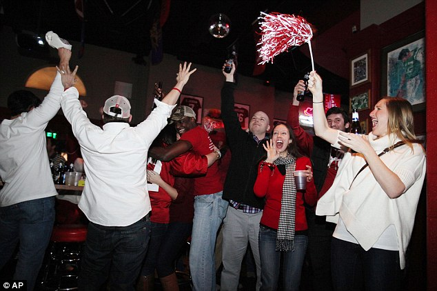 Alabama fans react as they watch a television broadcast of the kickoff of the BCS National Championship college football game against Notre Dame at Houndstooth Sports Bar in Tuscaloosa, Alabama