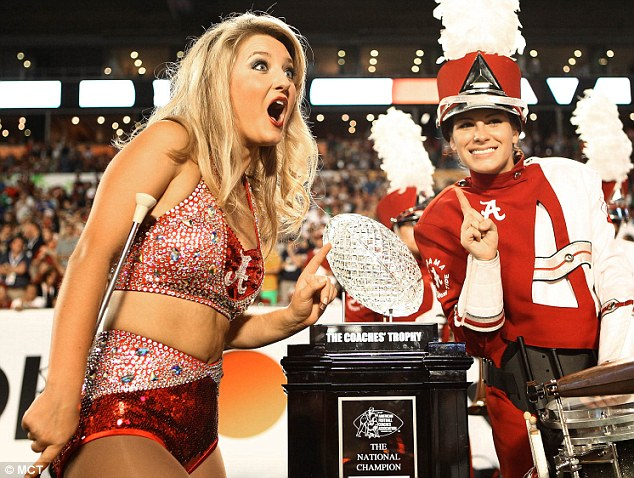 An Alabama cheerleader reacts while posing for a photograph with the BCS trophy at the start of the BCS Championship game against Notre Dame at Sun Life Stadium on Monday, January 7, 2013, in Miami Gardens