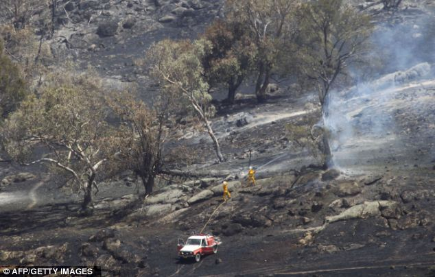 Fire fighters battle a grass fire in Oura