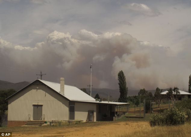 Wildfire smoke can be seen rising from hills behind the village of Numeralla