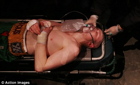 Fears: Farrell receives medical attention on a stretcher as he collapsed after the fight, he was later taken to hospital