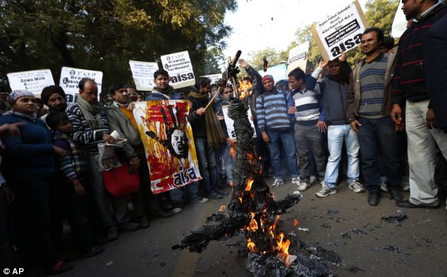 Fury: Indian students burn an effigy representing Hindu religious leader Asaram Bapu after he said on Monday that young rape victim in Delhi was as equally responsible for her rape as the rapists