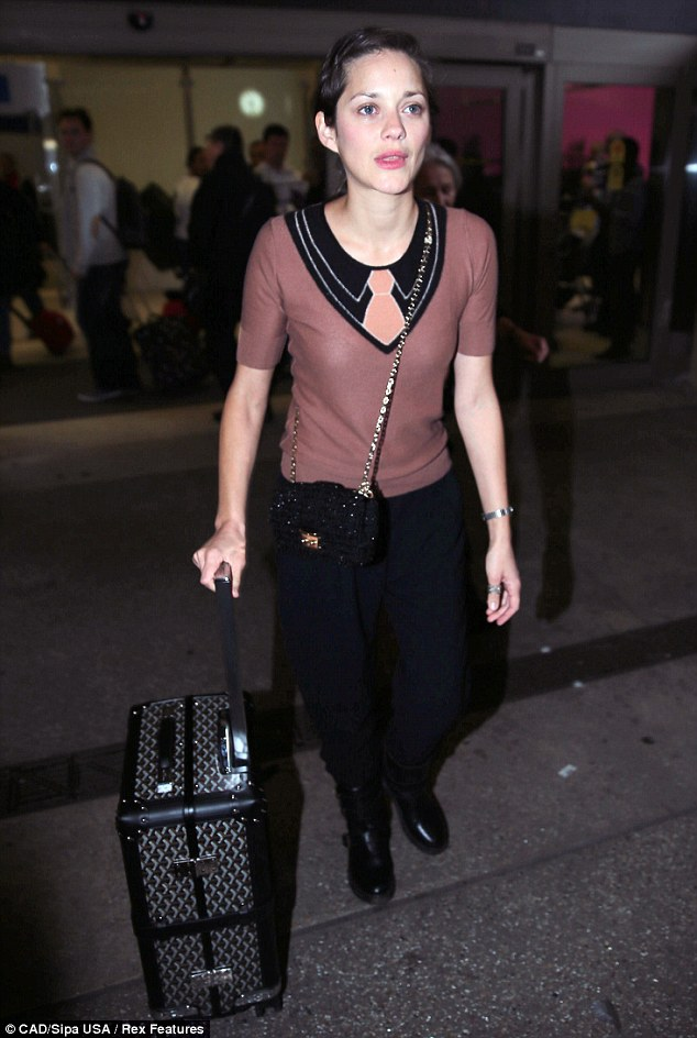 A different look: Fresh-faced Marion showed off her make-up free look as she arrived at LAX on Wednesday
