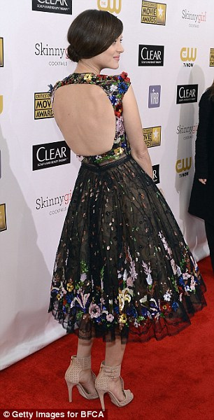 Peek-a-boo: The actress' sheer cap sleeve top with a skin-flashing cut out at the back combined with a modest length skirt made the flower-embroidered dress the perfect blend of sexy and sophisticated