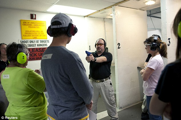 Controversial stance: Magowan (center) wields a rubber training pistol to demonstrate a shooting stance to his students at the Veritas Training Academy