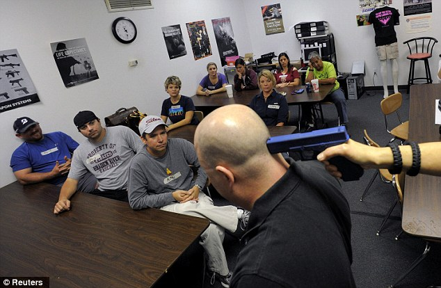 Risky business: Firearms instructor Mike Magowan (center) uses a rubber training pistol to demonstrate how to disarm a person holding a gun to one's head as he speaks to students