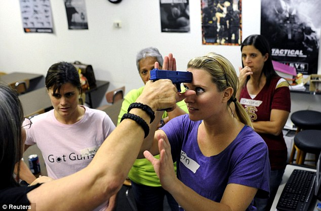 Jarring scene: A teacher in Sarasota, Florida, is learning how to disarm a gunman holding a plastic weapon to her head during a free training session