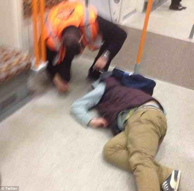 Collapse: A transport worker tries to rouse a young man who has fallen asleep fully clothed on the ground