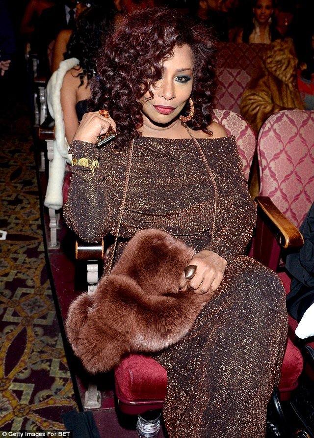 Glamour girl: Khan showed up in a glitzy brown gown and fur hand warmer