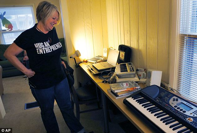 Entrepreneur Synthia Payne stands in her workspace at The Home for Hackers collaboration in Kansas City, Kansas. Payne moved to Kansas from Denver as her business plan is dependent on a fast internet connection
