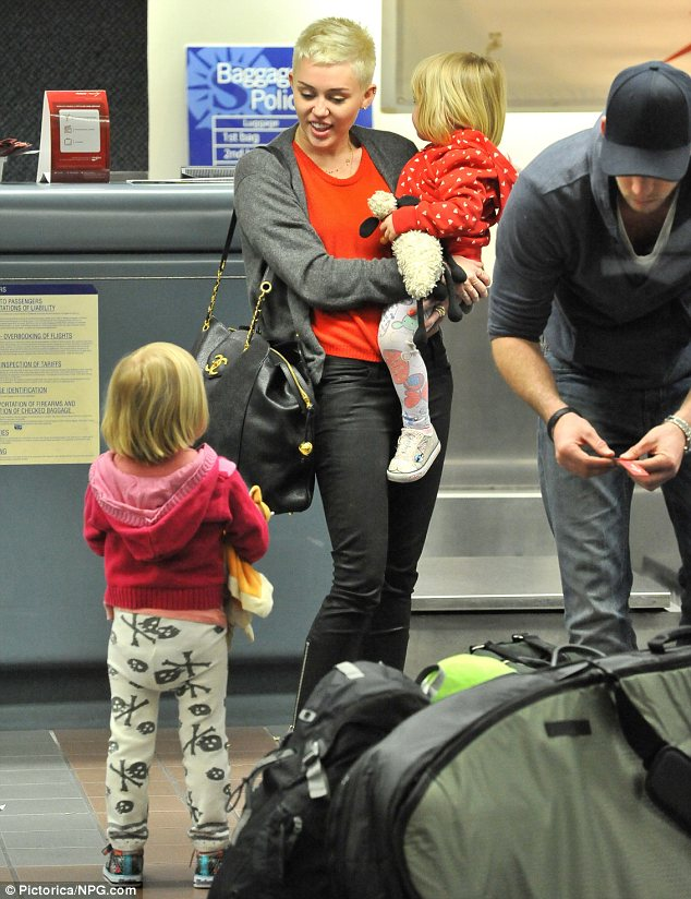 Practising for parenthood?: Miley was charged with taking care of Holly and Ella and took turns carrying them