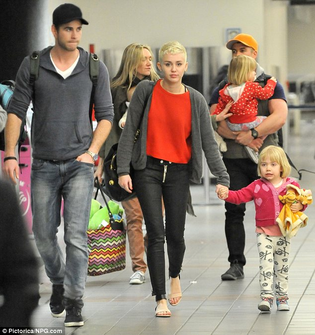 One of the gang: Miley Cyrus showed she's a member of the family as she headed on holiday with Liam Hemsworth, his brother Luke, sister-in-law Samantha and three nieces