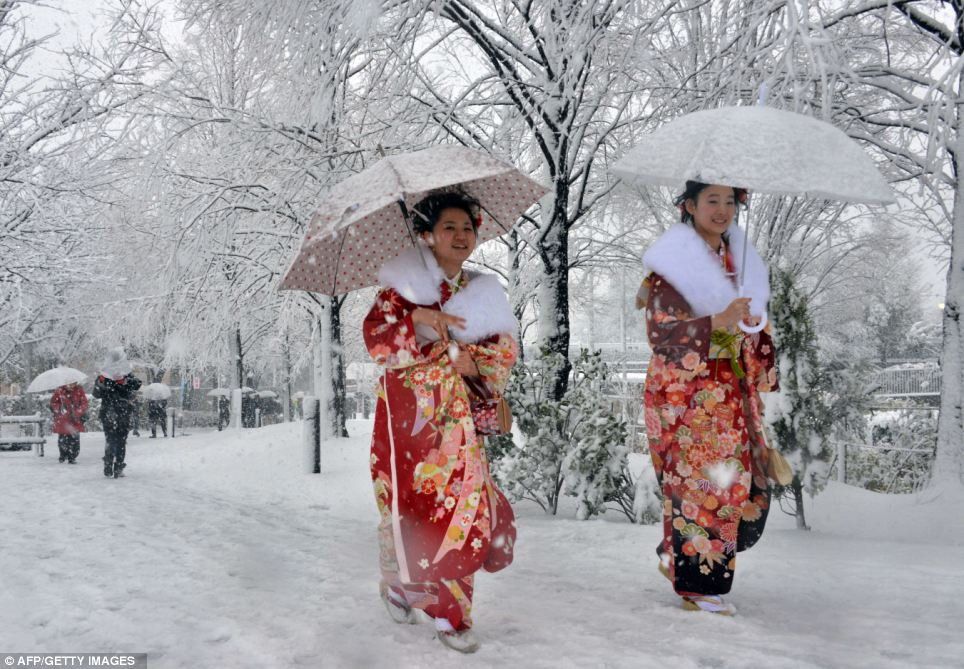 Picture perfect: The young women trudge through heavy snow in traditional costume - but their smiles stay in place