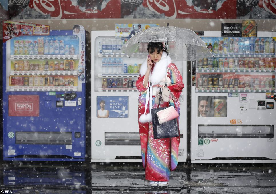 Blend is beautiful: A young woman in a rainbow-bright outfit stands talking on her phone in front of a line of vending machines - a symbol of Japan today