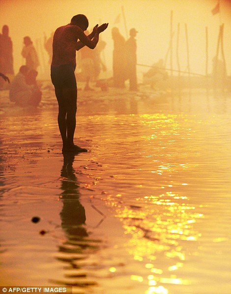 Dawn: A devotee is up at the break of day to pay his respects to the gods in Allahabad