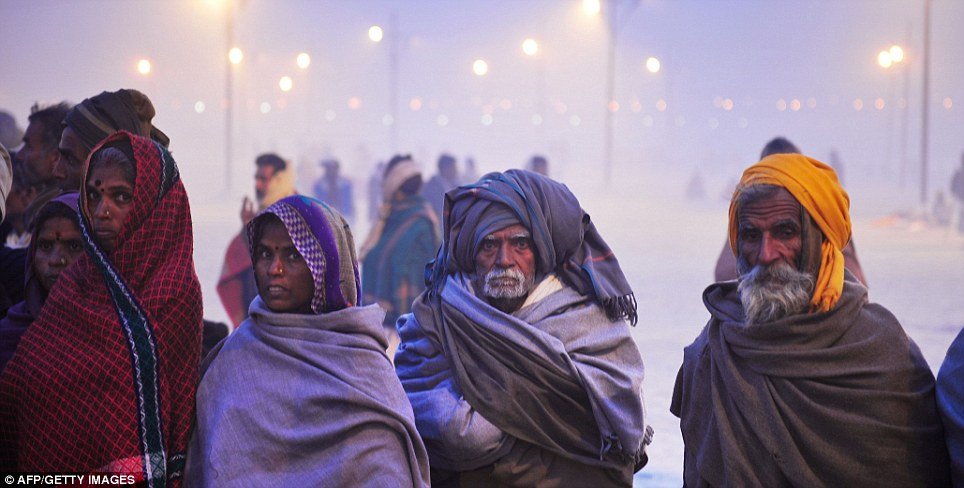 Devotees: Tens of thousands of Hindus gather to watch a procession of holy men during the vast festival