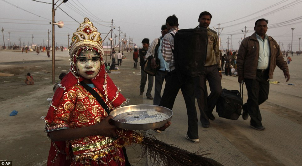 Ornate: An Indian girl dressed as Hindu Goddess begs for alms as devotees leave after a dip  at Sangam