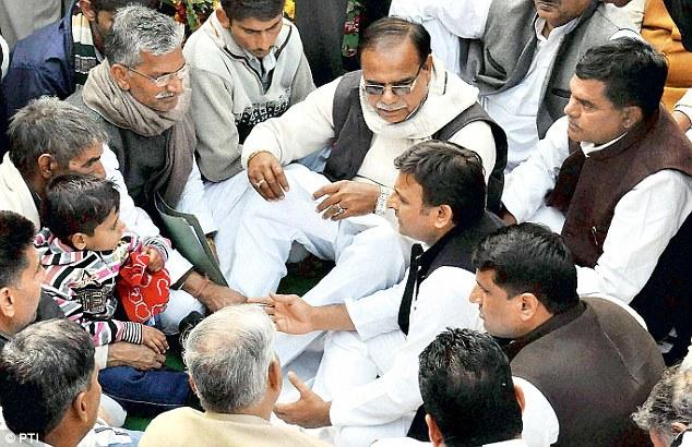 Uttar Pradesh Chief Minister Akhilesh Yadav talks with family members of Lance Naik Hemraj Singh outside his home in Mathura district
